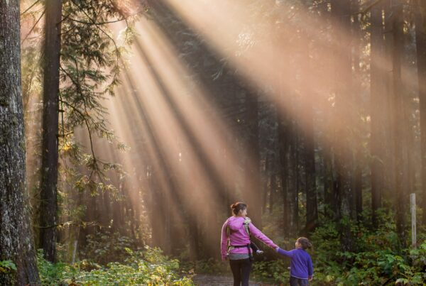 Image of a Mother and her son in forest with bright sun